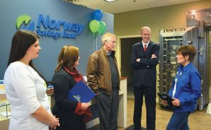 SEN. ANGUS KING, center, talks with, from right, bank manager Lennie Burke; Dan Walsh, vice president of community lending; Pam Bowerman, and Katie Chandler during a visit Friday at Norway Savings Bank's Maine Street location in Brunswick. King presented the bank with a special Congressional Record citation on the occasion of the institution's 150th anniversary.