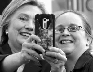 DEMOCRATIC PRESIDENTIAL CANDIDATE Hillary Clinton holds the phone to take a selfie with an employee at Market Basket Supermarket Tuesday in Manchester, New Hampshire.