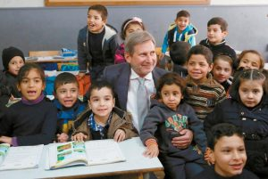 EUROPEAN COMMISSIONER FOR REGIONAL POLICY JOHANNES HAHN sits for a photo with Syrian students during his visit to a school in Beirut, Lebanon, in this Jan. 29 photo. International aid to the victims of Syria's five-year-old war, including millions forced to flee their homes, has persistently fallen short, but organizers of Thursday's annual Syria pledging conference hope for greater donor generosity this time around, despite a record ask of close to $9 billion for 2016.