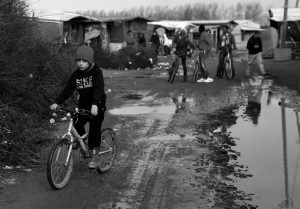 """A CHILD RIDES HIS BICYCLE in a makeshift camp for migrants near Calais, France, Thursday. The clock is ticking for some hundreds of migrants waiting for a judge to decide whether to postpone an eviction order in the camp locally referred to as """"the jungle."""""""