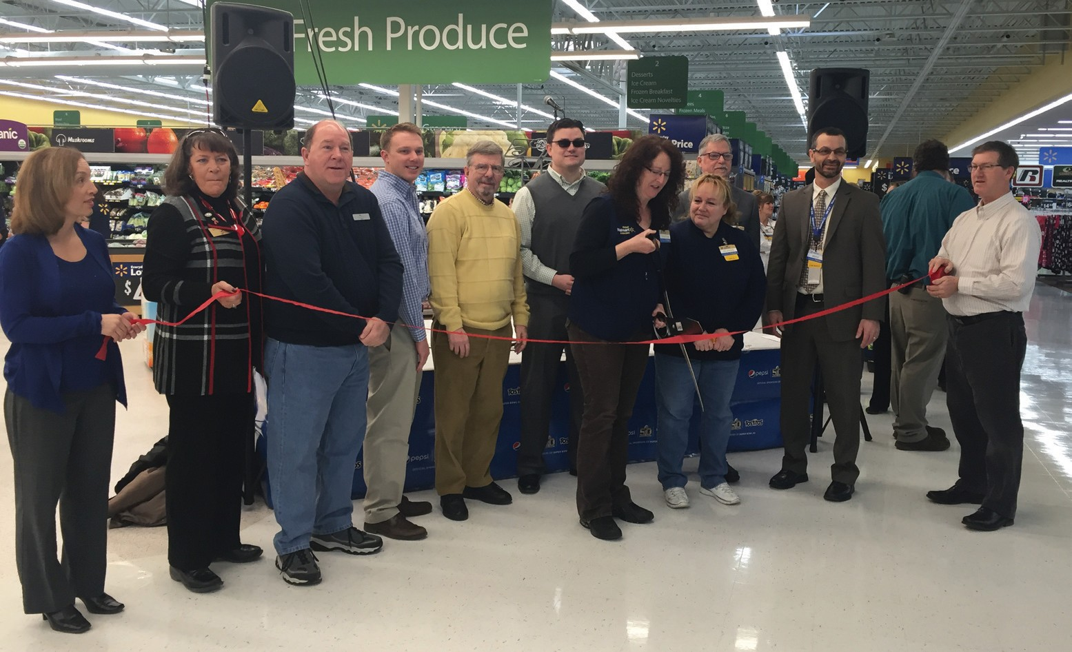 Walmart employee Christine Morin cuts a ribbon this morning at the Biddeford store in celebration of the completion of a remodel that began in September. With Morin are other Walmart employees as well as representatives from the Biddeford + Saco Chamber of Commerce + Industry.