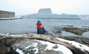 DAVE CLEAVELAND and his son, Cody, photograph the USS Zumwalt as it passes Fort Popham in Phippsburg at the mouth of the Kennebec River on Monday. The new destroyer, which was built at Bath Iron Works, is undergoing final builder trials before the ship is presented to the Navy for inspection.
