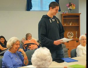 SMILES WERE SHARED on Thursday as Morse High School student Michael Coffin reads a biography he wrote about Plant Memorial Home resident Adrienne Flyna, on the left.