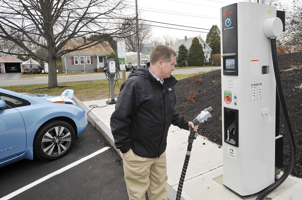 South Portland City Manager Jim Gailey checks out the high-speed charging station as he recharges his department's new Nisson Leaf at a slower charging station at the South Portland Community Center. Maine is working with Quebec to develop a corridor of electric car charging stations.