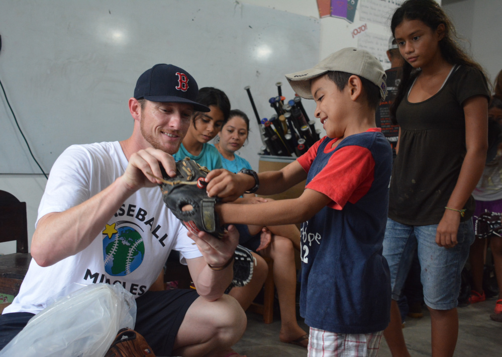 Michael McCarthy gives a young boy his first glove while on a January visit to Honduras. All of the equipment is donated, with McCarthy leading an annual equipment drive with the Portland Sea Dogs at Hadlock Field.