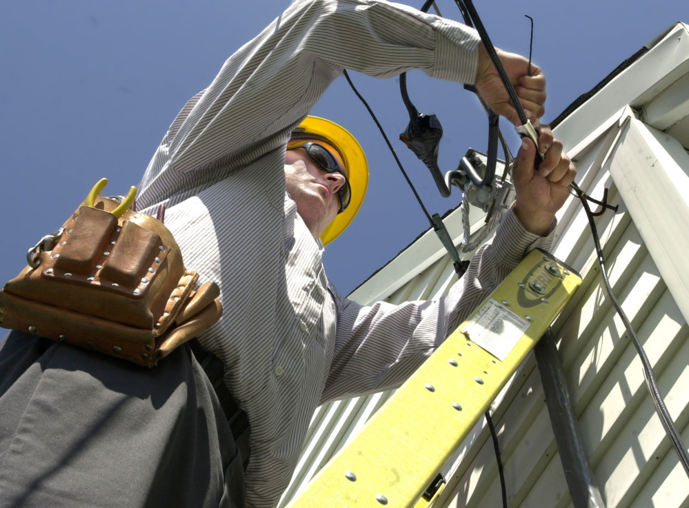 Dave Jackson works on a home cable service installation. Some cannot afford Internet access without the help of subsidies.