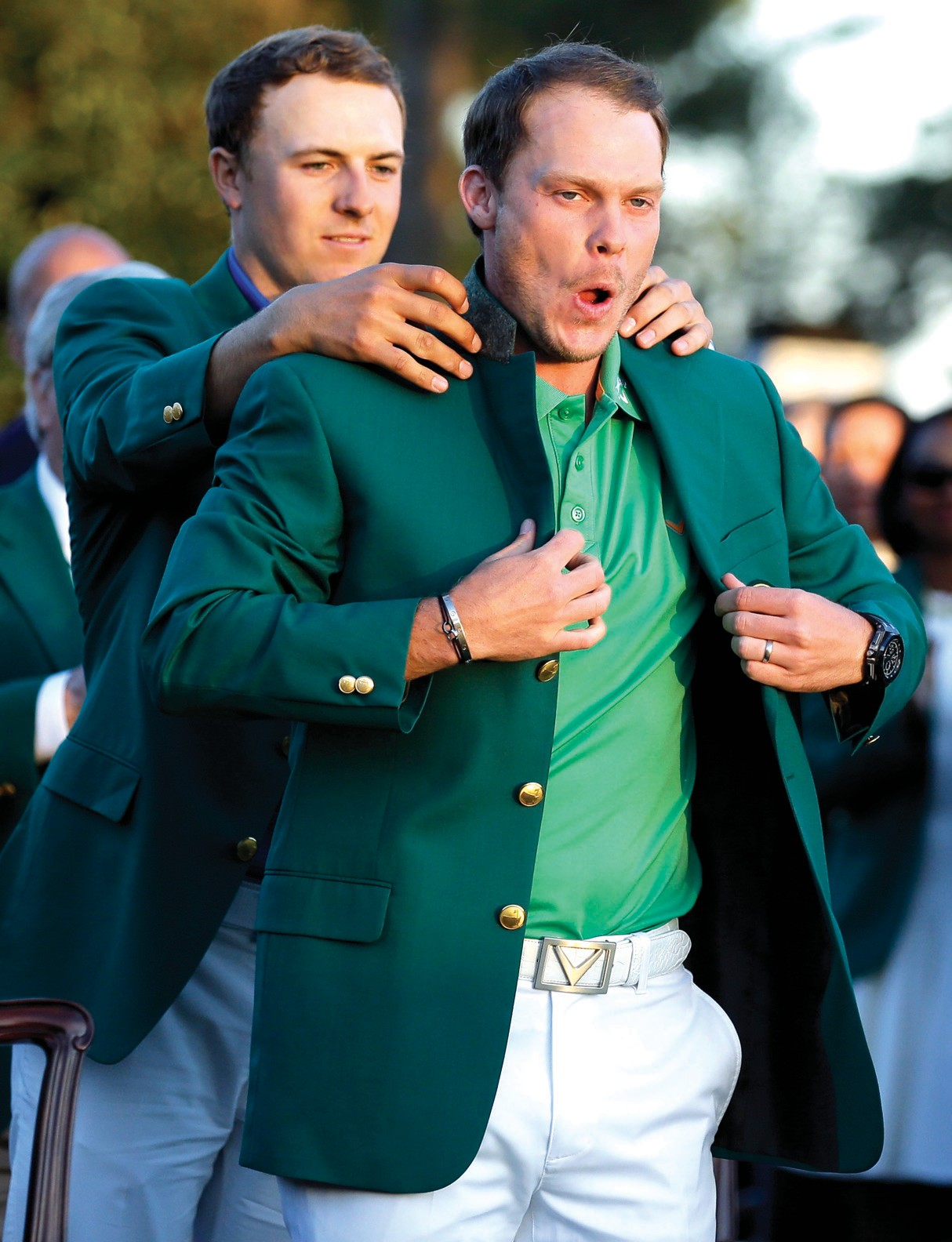 Defending champion Jordan Spieth, left, helps 2016 Masters champion Danny Willett, of England, put on his green jacket following the final round of the Masters on Sunday.