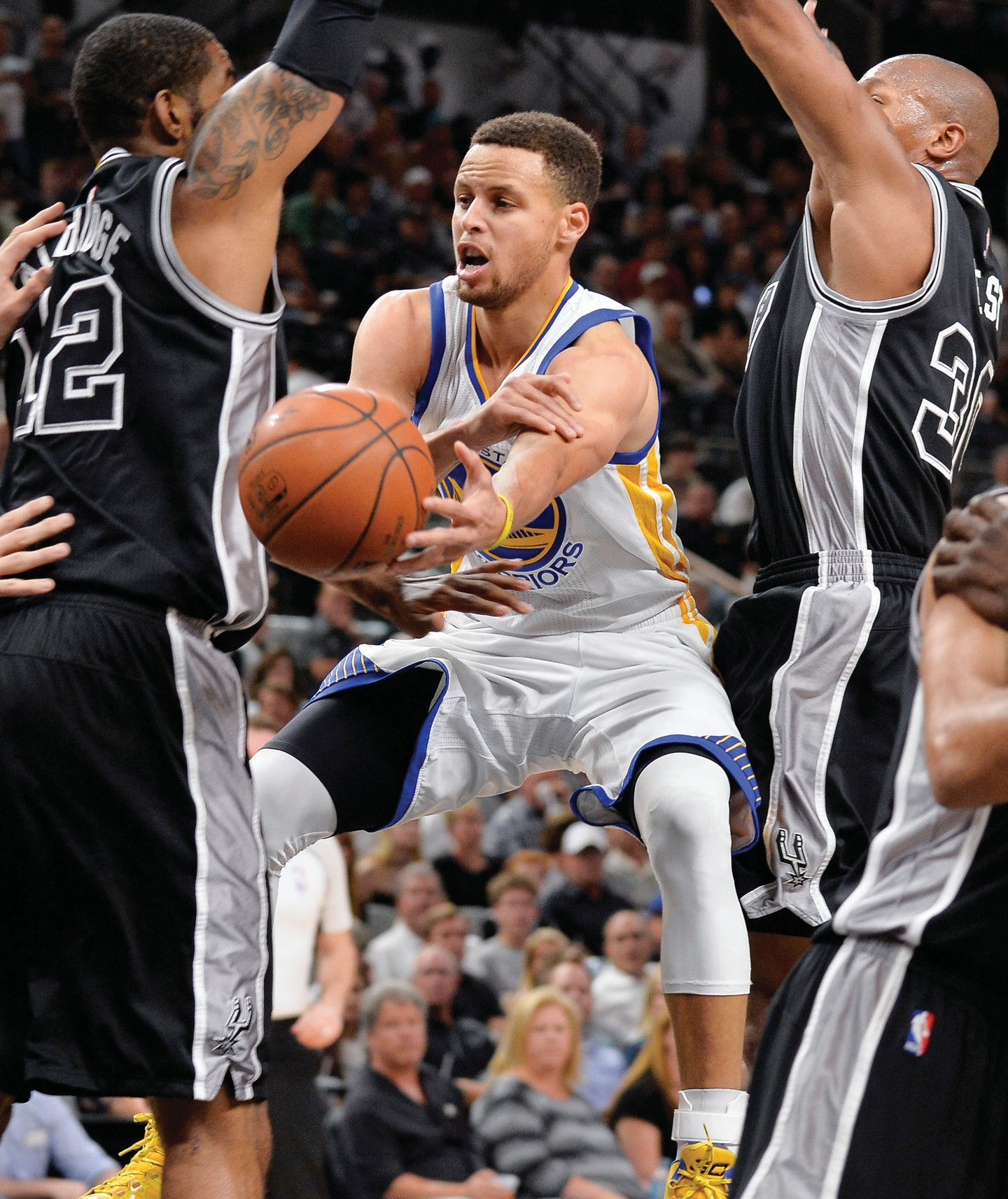 Golden State Warriors guard Stephen Curry, center, passes between San Antonio Spurs' LaMarcus Aldridge (12) and David West during the first half on Sunday.