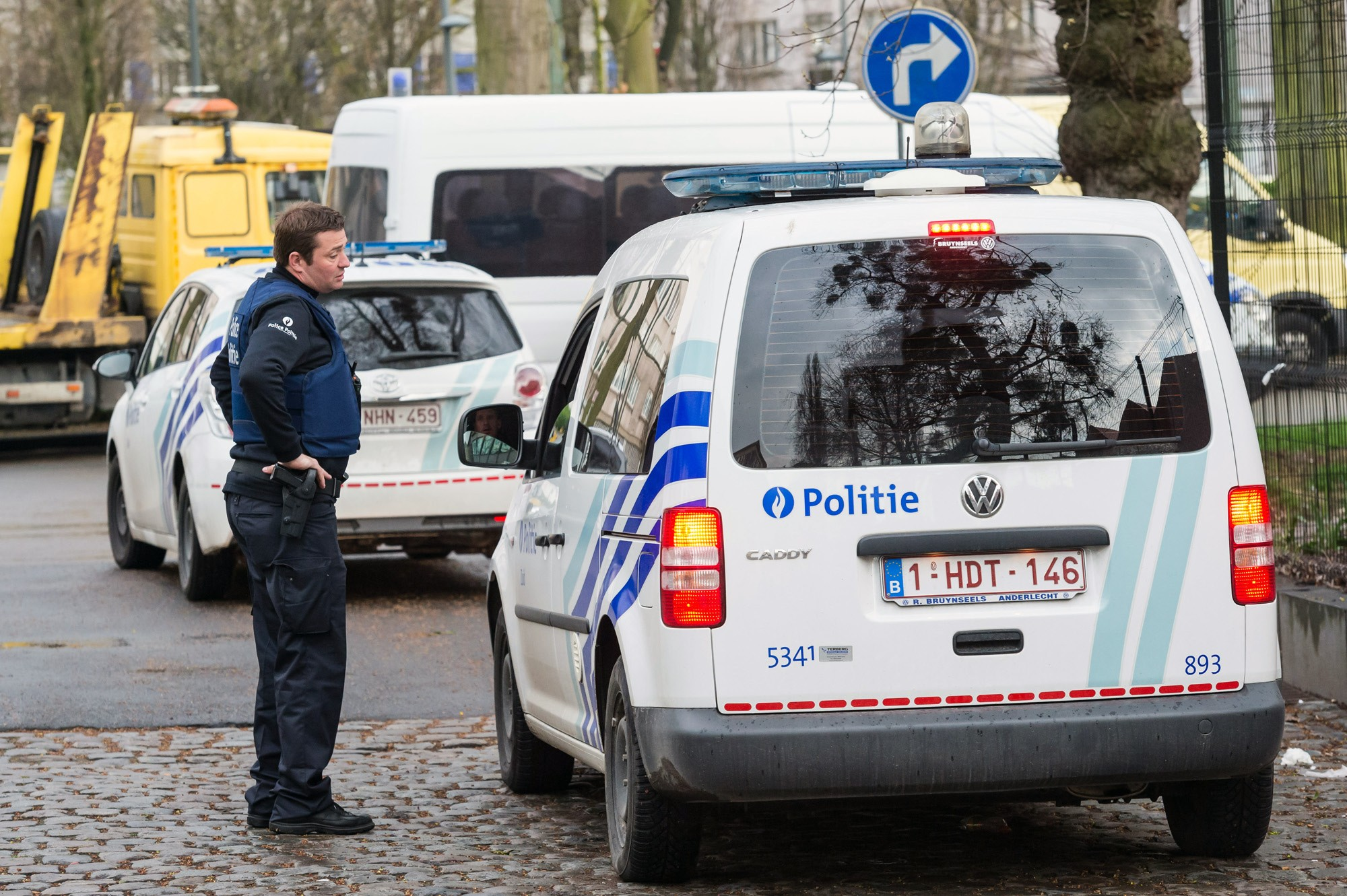 """Police secure an area where two terror suspects were arrested in Brussels on Friday. One of the men arrested, Mohamed Abrini, is believed to be the mysterious """"man in the hat"""" who escaped the double bombing at the Zaventem airport, according to one of the French officials."""