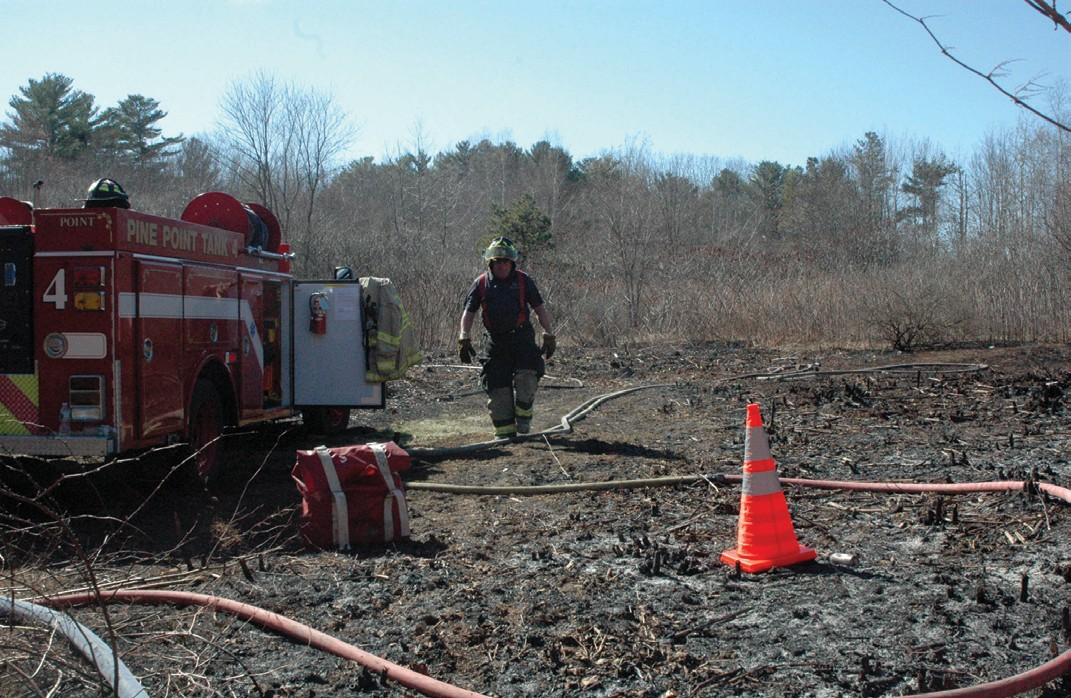A firefighter walks on burned debris after a brush fire in Old Orchard Beach Thursday afternoon.