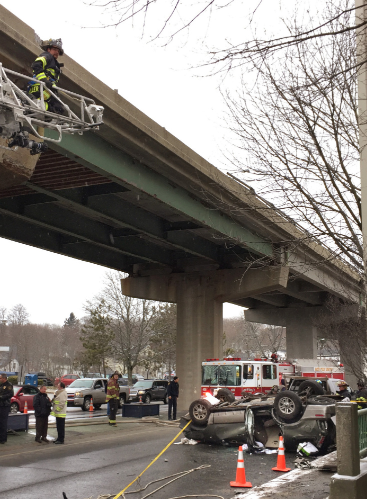A Mercury Mountaineer rests on its roof in Bath after falling off the Route 1 viaduct Monday. A woman and her son were pulled from the SUV and transported to Maine Medical Center in Portland.