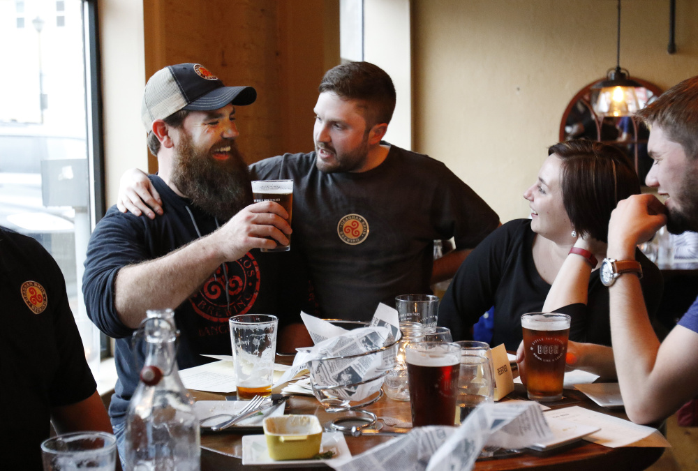 Andy Geaghan of Bangor's Geaghan Brothers Brewing, left, Chris Bougie and Lisa Sturgeon raise a glass at the Little Tap House after the inaugural New England Brew Summit in Portland last Friday. The high quality of Maine beers is drawing aficionados from around the world.