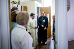 Rev. Paul Dumais meets with Mass attendees in the sacristy of the chapel at the d'Youville Pavillion at St. Mary's Hospital in Lewiston.