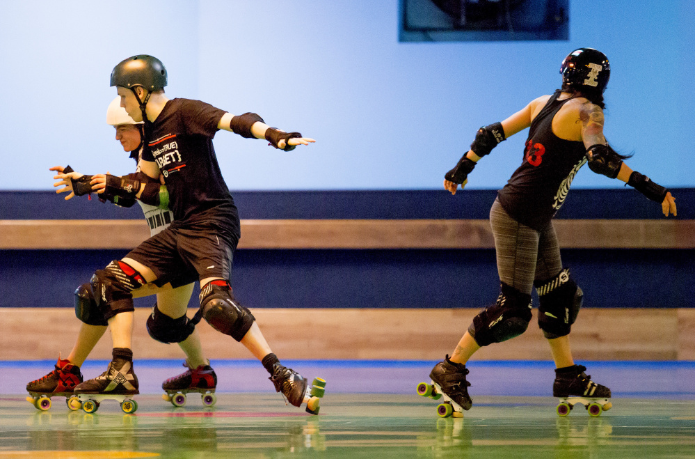 "Leah ""Cabbage Smash Kid"" Farber, PJ ""Shazzama Pajama"" Koroski and Heather ""Kirsten Damned"" Tirado – members of the Maine Roller Derby league – practice Wednesday at Happy Wheels on Warren Avenue in Portland."