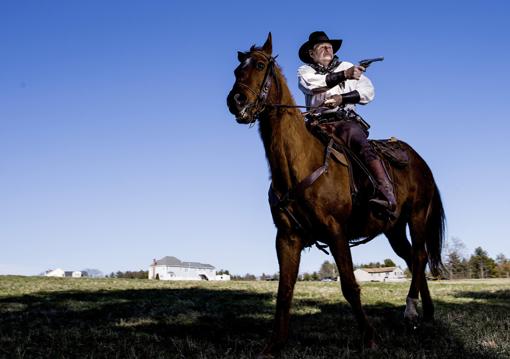 Bill Ledoux, president of the Maine Mounted Cowboy Shooters, poses at his Biddeford home Wednesday with his registered quarter horse Teddy. The Saco City Council is considering amending the city's firearms ordinance to allow Western-style shooting, like what Ledoux performs with Teddy.