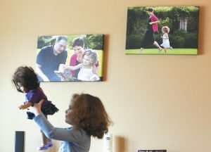 BRIANNA MCMANAMY, 4, plays with her doll, Sweetie, in the living room where photos of her, with her mother Heather and father hang on the wall in the background at their home in McFarland, Wisconsin.