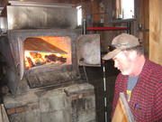 Russell Parsons keeps the wood fire burning last week to boil sap.