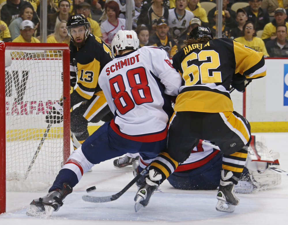 Pittsburgh's Carl Hagelin, right, deflects the puck past Washington's Nate Schmidt for a second-period goal during the Penguins' 3-2 playoff win Monday at Pittsburgh.