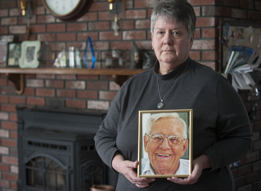 Kathy Day stands with a portrait of her father, John P. McCleary Sr., in her Bangor home Wednesday. McCleary died of a preventable hospital-acquired infection in 2009.