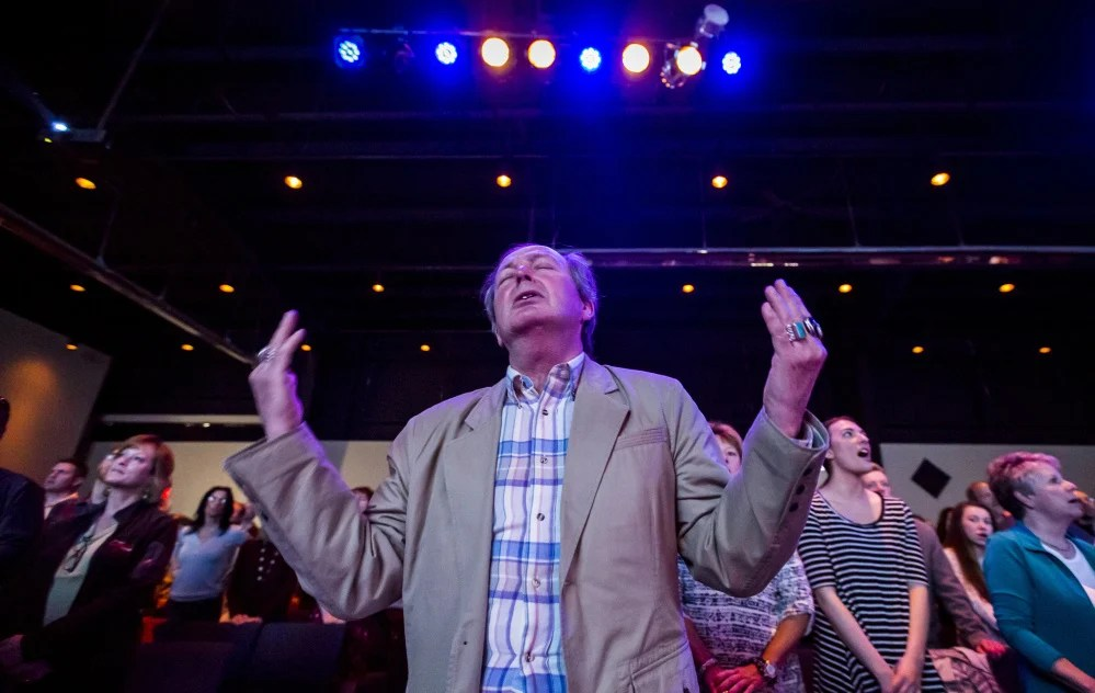 Paul Hancock of Naples sways to the music at Eastpoint Christian Church at a recent service in Portland. Weekly attendance has grown to 1,300 in a little more than a decade, prompting leaders to plan an ambitious $7 million move to a former big-box store in South Portland.