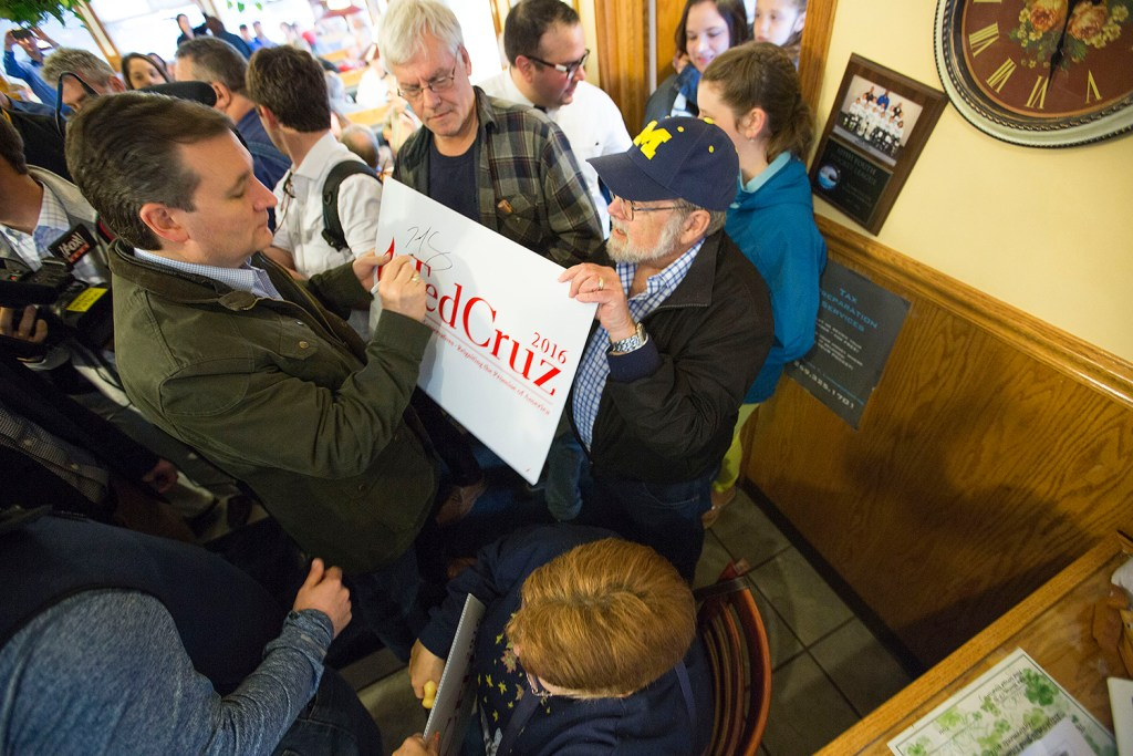 Ted Cruz, left, signs a campaign sign for a supporter inside the Bravo Cafe in Osceola, Ind. Monday, The Associated Press/Sam Householder/The Elkhart Truth