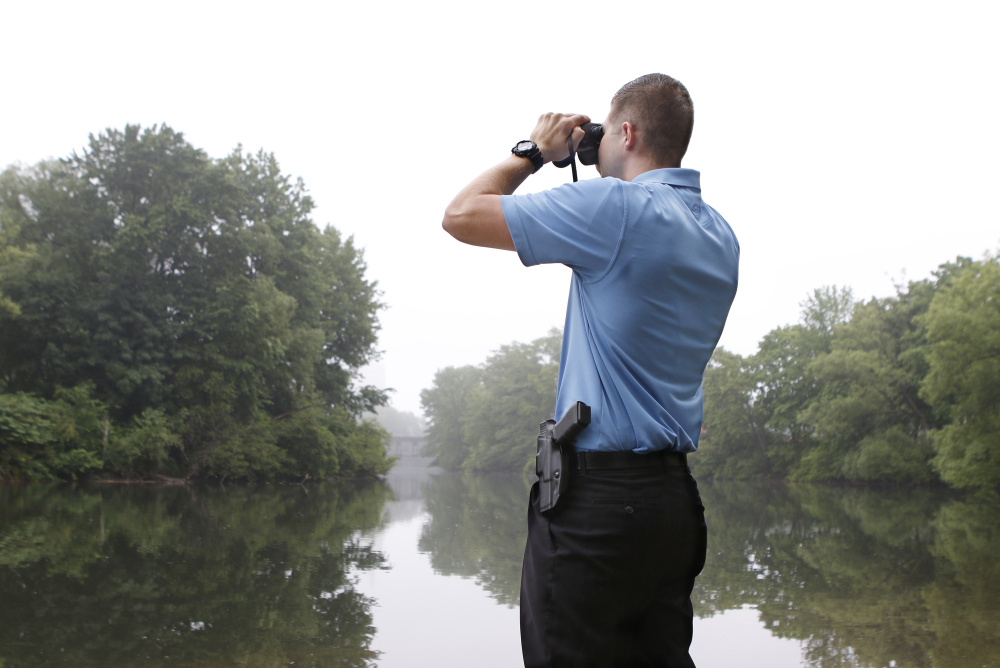 Police officer Garrett McCarthy scans the Presumpscot River's banks in Westbrook on Wednesday, looking for a non-native species of snake believed to be lying dormant after eating a beaver.