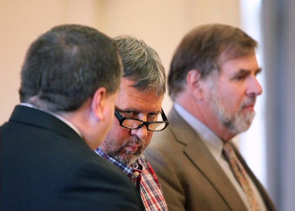 Bruce Akers, 57,  of Limington, center, who pleaded not guilty Tuesday on a charge of murdering his neighbor Douglas Flint, is shown in his initial appearance in York County Superior Court on June 13, 2016. At left is attorney Robert LeBrasseur and at right is attorney Paul Aranson.
