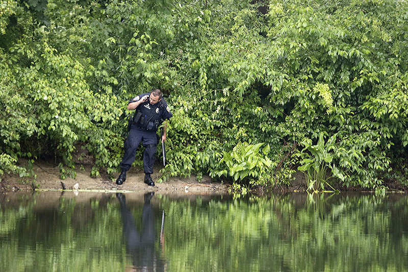 Officer Phil Robinson looks along the Presumpscot River in Westbrook after reports of a 10-foot-long snake seen eating a beaver.
