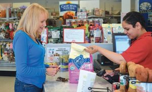 PAULINE SOUTER of Bath buys dog food from Pet Quarters' employee Aprille Marie of Brunswick. Souter said she was sorry to hear the Brunswick store was closing.