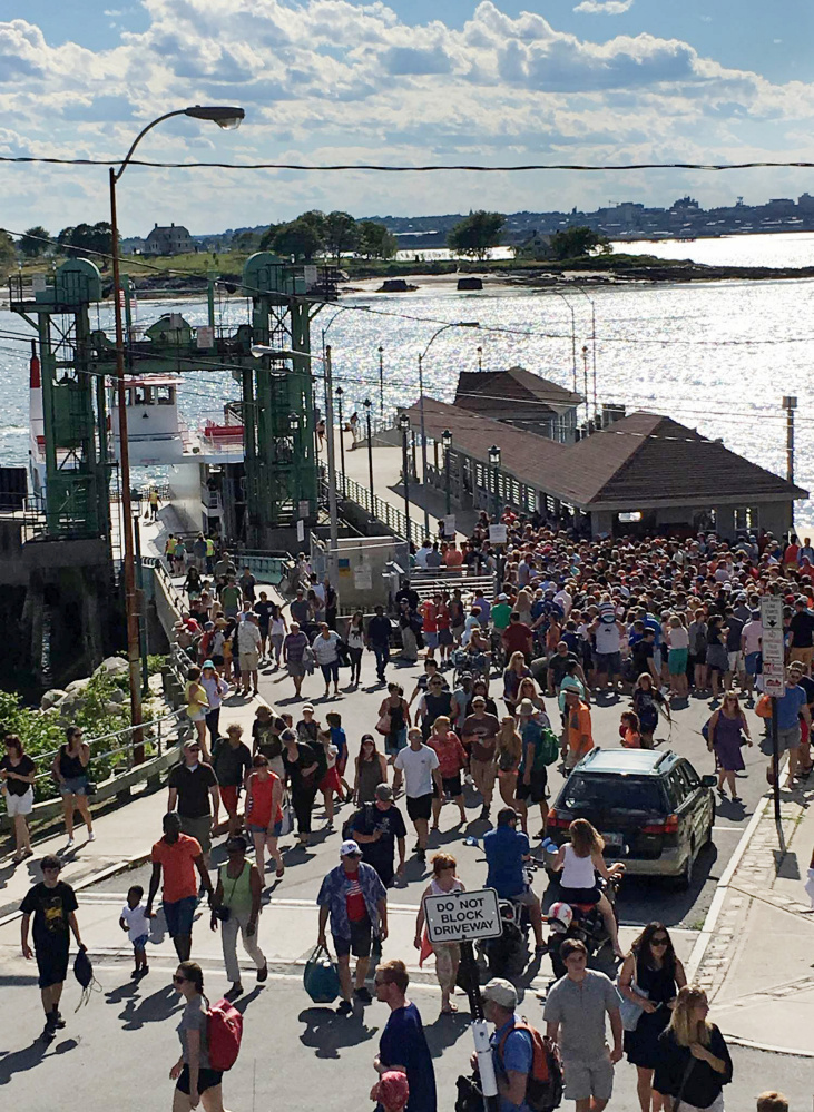 Passengers stream from the ferry landing July 3 on Peaks Island. Recent heavy use of the ferry has some islanders thinking Peaks residents should get boarding priority.