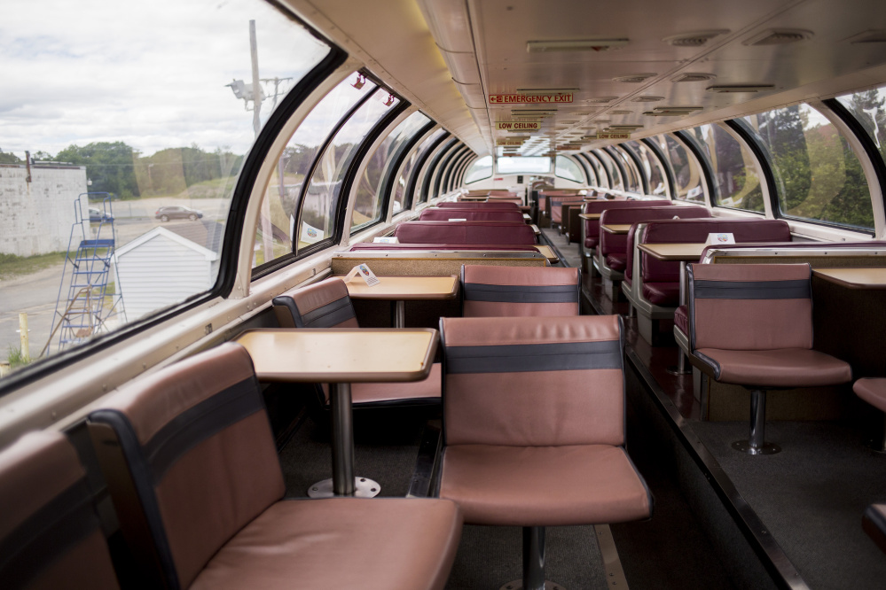 The interior of the 70-year-old dome car contains a lounge with padded swivel chairs, tables and benches, all encased in a glass dome that gives riders a 360-degree view of the scenery. as the train travels between Portland and Boston.