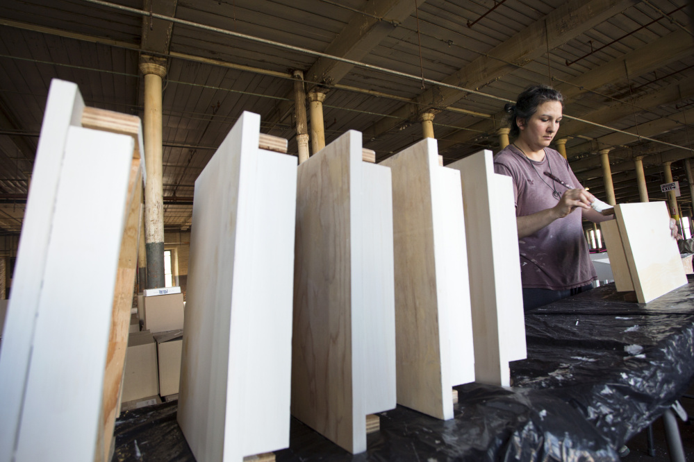 """Amy Stacey Curtis works on one of the 99 desks that are part of the """"Memoir"""" component of """"Memory."""""""