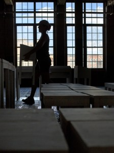 Assistant Cheyanne MacDougall at work on the installation with a view from the windows of the Bates Mill complex.