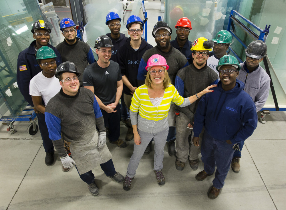 Cindy Caplice, human resources manager at the Sigco fabricating company in Westbrook, stands with some of her workers. Caplice says a focus on hiring African immigrants has been an unqualified success for the company.