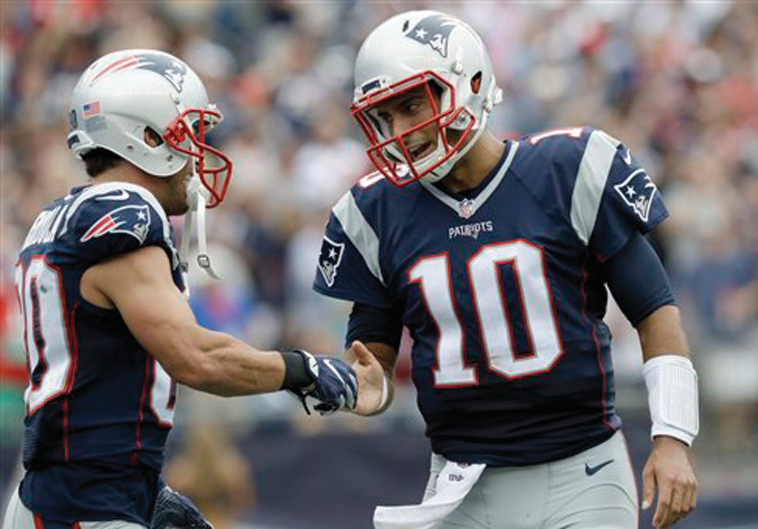 New England Patriots quarterback Jimmy Garoppolo (10) and wide receiver Danny Amendola (80) celebrate their touchdown pass completion against the Miami Dolphins during the first half of an NFL football game Sunday, in Foxborough, Mass.
