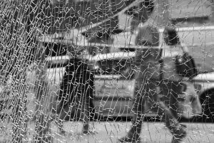 NEW YORKERS pass a shattered storefront window on W. 23rd St. in Manhattan Tuesday in New York. The window was hit by shrapnel from the terrorist bomb that exploded across the street Saturday evening. An Afghan immigrant wanted in the bombings was captured Monday after being wounded in a gun battle with police.