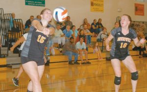 BRUNSWICK HIGH SCHOOL girls volleyball player Katharine Kunhardt (15) makes a pass while teammate Julia Baumgarte looks on during a match with Falmouth at Harriet Beecher Stowe Elementary School in Brunswick on Tuesday. The Dragons battled hard in a 3-0 loss to Falmouth.