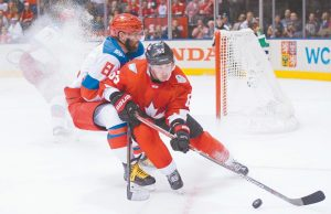 TEAM CANADA'S Brad Marchand (63) and Team Russia's Alex Ovechkin (8) battle for the puck during the third period of a World Cup of Hockey semifinal game last Saturday in Toronto. Marchard signed a new long-term deal with the Boston Bruins on Monday.