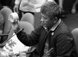 FORMER FILIPINO MILITIAMAN EDGAR MATOBATO shows the kind of tape they use to wrap up dead bodies as he testifies before the Philippine Senate in Pasay, south of Manila, Philippines today. Matobato said that Philippine President Rodrigo Duterte, when he was still a city mayor, ordered him and other members of a squad to kill criminals and opponents in gangland-style assaults that left about 1,000 dead.