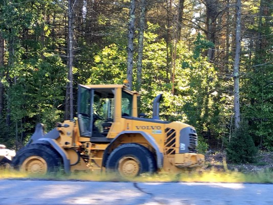 A stolen front-end loader sits on the side of the Maine Turnpike after it hit several cars on Monday morning. Photo by WCSH-TV