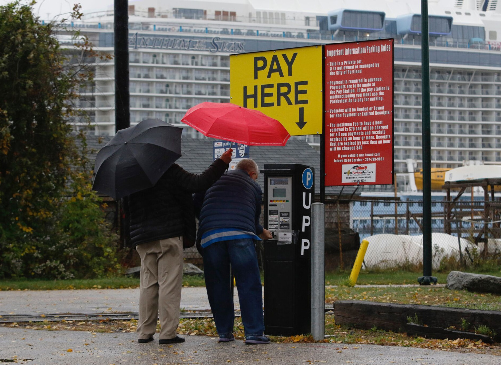 People pay for parking in a lot near the Anthem of the Seas on Sunday. The $940 million ship, which holds up to 4,905 passengers on its 18 decks, stopped in Portland several times this fall as cruise ships have become a plus for the state's tourism industry.