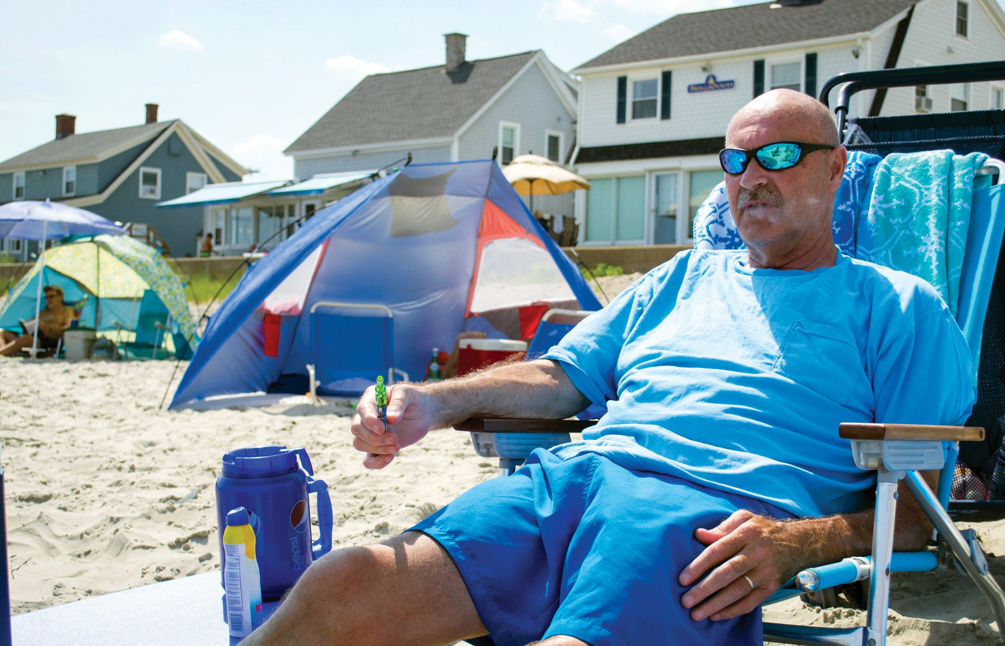 Mark Rowen of Burlington, Vt., smokes from a vaporizer pen at Wells Beach in this photo from August. The town on Tuesday passed an ordinance banning smoking of tobacco and plant products in all forms on town beaches.