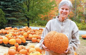 SHIRLEY REESE of the Mid-Coast Presbyterian Church in Topsham stands with one of her favorite pumpkin varieties at the church's pumpkin patch on Thursday.