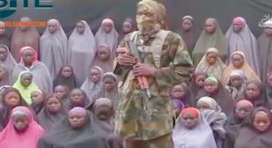 AN ALLEGED BOKO HARAM SOLDIER stands in front of a group of girls alleged to be some of the 276 abducted Chibok schoolgirls held since April 2014, in an unknown location, in this undated image taken from video distributed Aug. 14. Twenty-one of the Chibok schoolgirls kidnapped by Boko Haram Islamic extremists more than two years ago have been freed in negotiations, officials said today. Some 197 girls remain captive, though it is not known how many of them may have died.