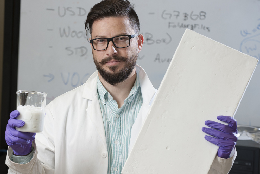 Nadir Yildirim holds a wood and water slurry and a sample insulation board made from the slurry at his University of Maine lab. The work he's doing shows how homegrown innovation can draw wealth to Maine.