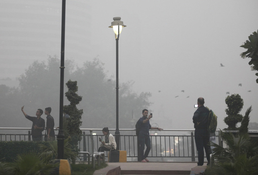 Indians take selfies at a public park enveloped by thick smog in New Delhi on Saturday.