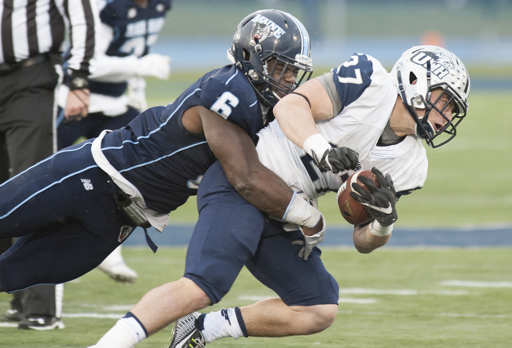 Christophe Mulumba Tshimanga of Maine brings down Dalton Crossman of New Hampshire during the second half of New Hampshire's 24-21 victory Saturday at Orono.