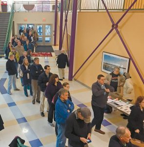 """PEOPLE LINE UP to vote early this morning at Freeport High School. """"It's either vote now or at the end of the day, and I get up early,"""" said Freeport resident Derek Libby. Christine Reynolds, also of Freeport, said, """"I didn't know when I was going to get out of work, and I didn't want to not vote."""" Polls are open until 8 p.m. this evening."""