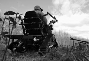 PARAPLEGIC HUNTER GARY DUPUIS of Ashburnham, Mass., waits in his all-terrain wheelchair, equipped with a shooting rack for his shotgun, while deer hunting in Devens, Mass. on Friday. The Massachusetts Division of Fisheries and Wildlife officials and volunteers have run a program that gets paraplegic hunters into the woods to hunt for deer during a special season.