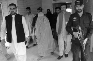 """PAKISTANI OFFICIALS escort famed Afghan woman Sharbat Gulla in a burqa or veil outside a court in Peshawar, Pakistan. A Pakistani government official says today National Geographic's famed green-eyed """"Afghan Girl"""" has been deported to Afghanistan. Fayaz Khan says Pakistani officials handed over Gulla and her four children to Afghan authorities early today at Torkham border, 37 miles northwest of Peshawar city."""